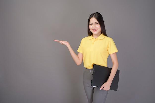 Młoda ufna piękna kobieta jest ubranym żółtą koszula trzyma dokumenty na szarość