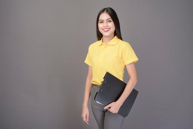 Młoda ufna piękna kobieta jest ubranym żółtą koszula trzyma dokumenty na szarym studiu