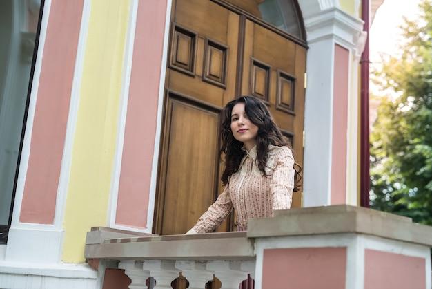 Młoda ukraińska kobieta w stylowej tkaninie w pobliżu nowoczesnego kolorowego budynku na ulicy miasta