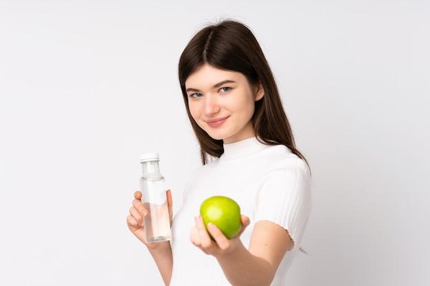 Młoda ukraińska nastolatek kobieta nad odosobnioną biel ścianą z jabłkiem i butelką wody
