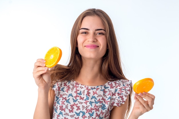 Młoda urocza brunetka z plastrami pomarańczy w rękach na białym tle