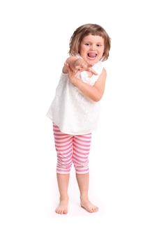 Młoda urocza dziewczyna próbuje dotrzeć do czegoś na białym tle