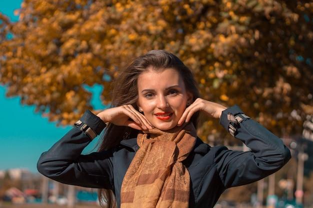 Młoda urocza dziewczyna stoi na ulicy, uśmiecha się i podnosi ręce do twarzy