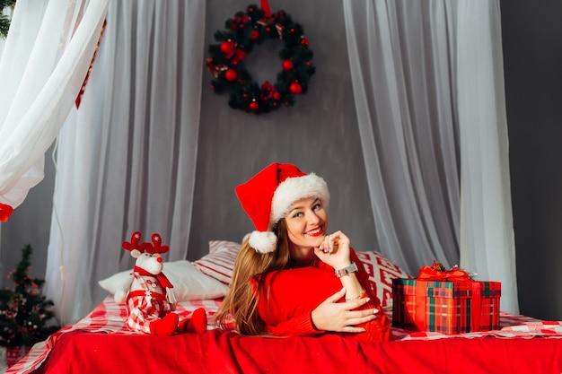 Młoda urocza dziewczyna w oczekiwaniu na święta, patrząc na kamerę