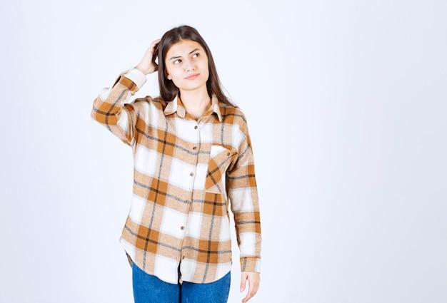 Młoda urocza dziewczyna w stroju casual pozowanie myślenia.