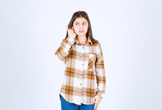Młoda urocza dziewczyna w ubranie pozowanie do kamery na białej ścianie.