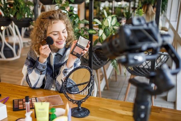 Młoda urocza kobieta pokazująca paletę makijażu w aparacie i nagrywająca swój film