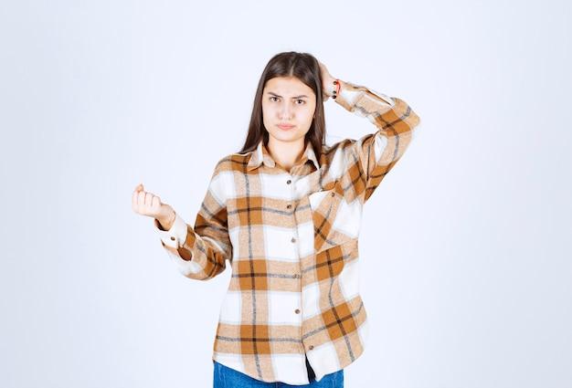 Młoda urocza kobieta stojąc na białej ścianie.