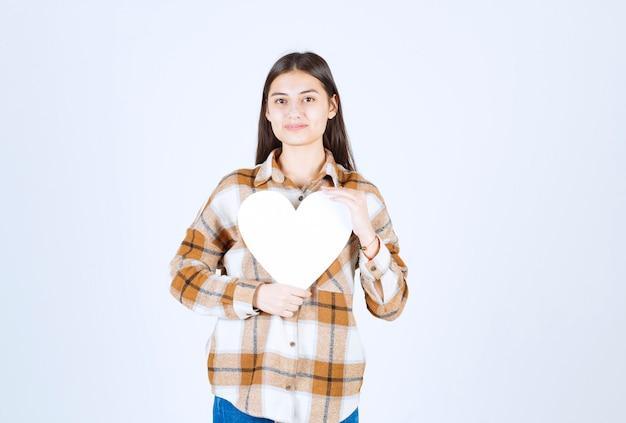 Młoda urocza kobieta trzyma papierową kartę w kształcie serca na białej ścianie.