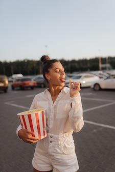 Młoda urocza kobieta trzyma popcorn na parkingu centrum handlowego