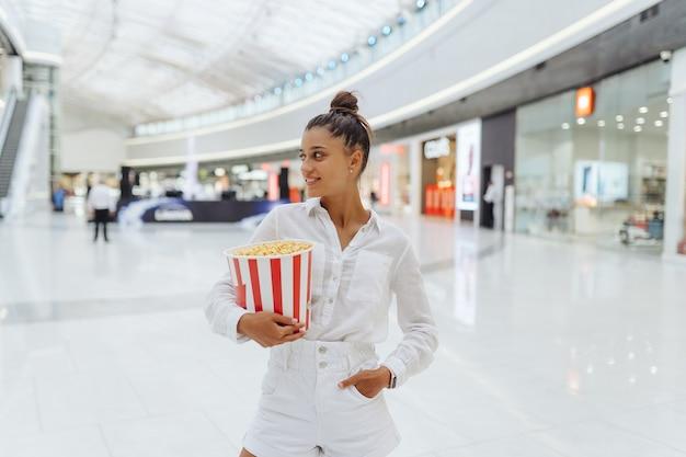 Młoda urocza kobieta trzyma popcorn w centrum handlowym