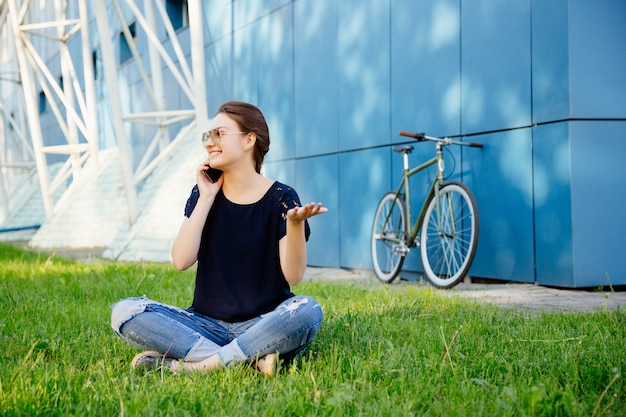 Młoda urocza kobieta w przypadkowych ubraniach siedzi na trawie i rozmawia przez telefon komórkowy, ciesząc się wolnym czasem, po spacerze z rowerem.