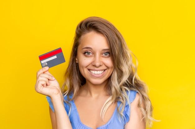 Młoda urocza kobieta z falującymi włosami trzyma w ręku plastikową kartę kredytową płatność za zakupy