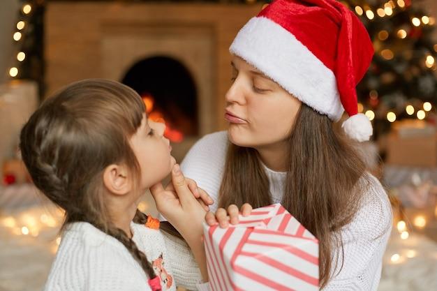 Młoda urocza mama i córka z pudełkiem, patrząc na siebie, chcą pocałować swoją uroczą małą dziewczynkę, w wigilię bożego narodzenia w domu, pozują przy kominku.