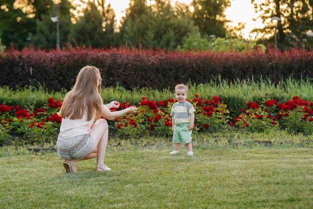 Młoda urocza mama pomaga i uczy swojego małego synka stawiać pierwsze kroki podczas zachodu słońca w parku na trawie.