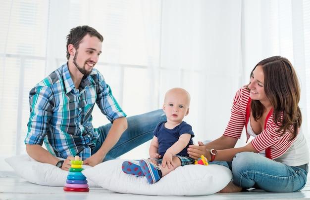 Młoda urocza mama, tata i syn bawią się razem w salonie w dzień wolny. szczęśliwa młoda koncepcja rodziny