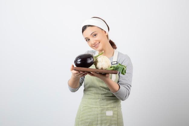 Młoda urocza modelka trzyma drewniany talerz z bakłażanem i kalafiorem