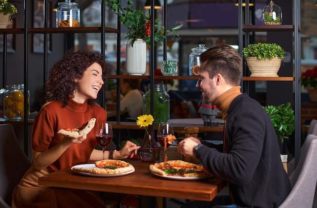 Młoda urocza para je pizzę w pizzerii. facet bawi swoją dziewczynę w restauracji. szczęśliwi ludzie bawią się razem