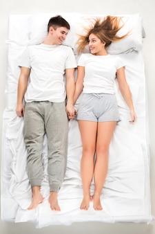 Młoda urocza para leżąca w łóżku
