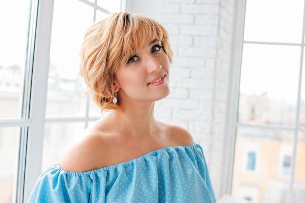 Młoda urocza uśmiechnięta blondynki krótkiego włosy kobieta