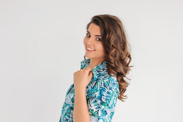 Młoda urocza uśmiechnięta brunetki dziewczyna z falistym włosy w lato sukni, odizolowywa na bielu