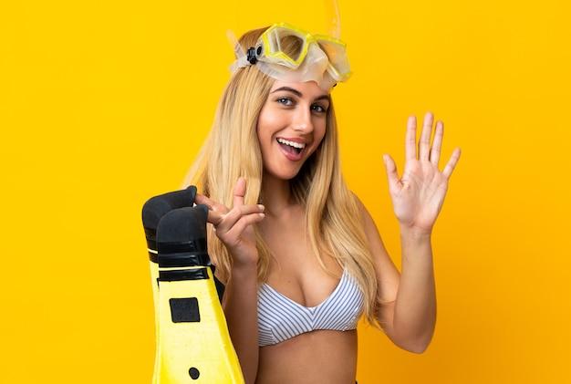 Młoda urugwajska blond kobieta w stroju kąpielowym trzyma płetwy i okulary do nurkowania w letnie wakacje, pozdrawiając ręką z szczęśliwym wyrazem twarzy