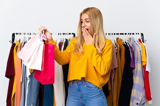 Młoda urugwajska blondynka w sklepie odzieżowym i trzymając torby na zakupy ze zdziwieniem i zszokowanym wyrazem twarzy