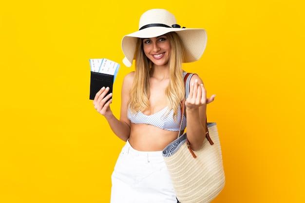 Młoda urugwajska blondynka w stroju kąpielowym trzyma paszport na odosobnionym żółtym tle zapraszając do przyjścia z ręką. cieszę się, że przyszedłeś