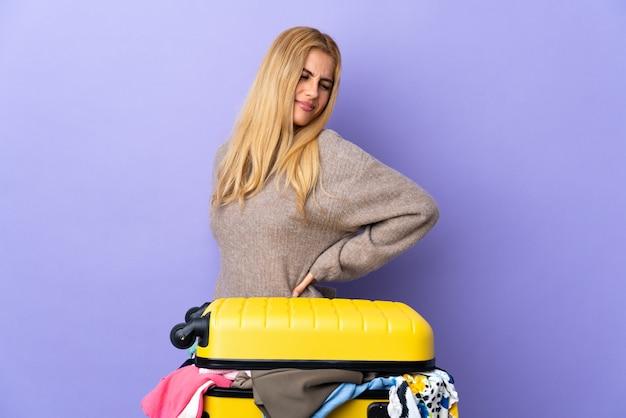 Młoda urugwajska blondynka z walizką pełną ubrań na izolowanym fioletowym murze cierpiącym na bóle kręgosłupa z powodu wysiłku