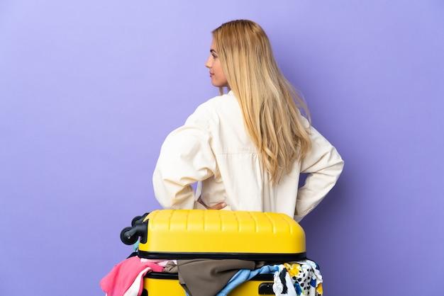 Młoda urugwajska blondynka z walizką pełną ubrań na odosobnionej fioletowej ścianie w tylnym położeniu i patrząc z boku