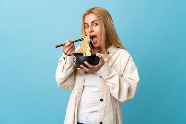 Młoda urugwajska blondynki kobieta nad odosobnionym błękitem trzyma puchar kluski z pałeczkami i je je