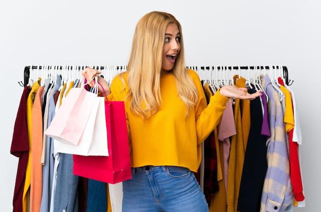 Młoda urugwajska blondynki kobieta w sklepie odzieżowym i trzymający torba na zakupy z niespodzianką wyrazem twarzy