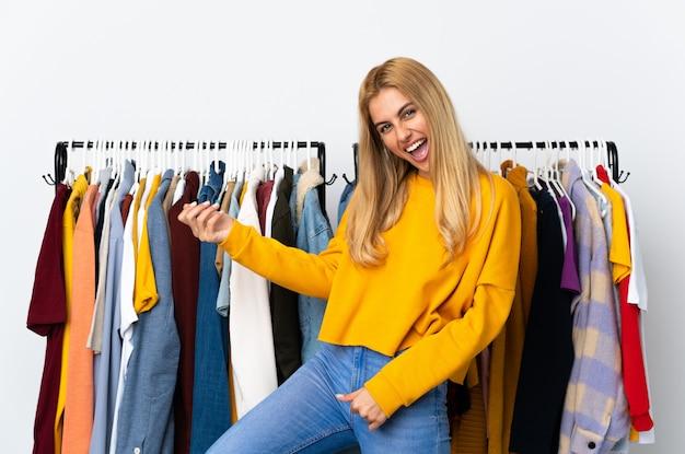 Młoda urugwajska blondynki kobieta w sklepie odzieżowym robi gitarze gestowi