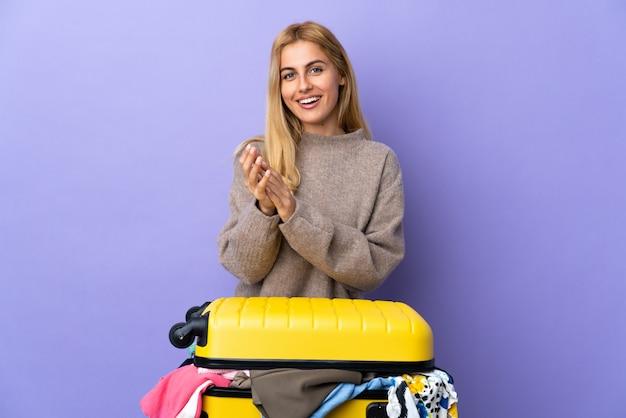 Młoda urugwajska blondynki kobieta z walizką pełną ubrań nad odosobnioną purpurową ścianą brawo po prezentacji na konferencji