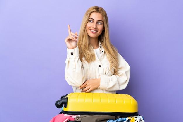 Młoda urugwajska blondynki kobieta z walizką pełną ubrań nad odosobnioną purpurową ścianą wskazuje w górę świetnego pomysłu