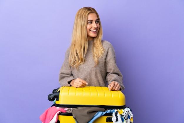 Młoda urugwajska blondynki kobieta z walizką pełną ubrania nad odosobnioną purpurą izoluje patrzeć z boku i ono uśmiecha się
