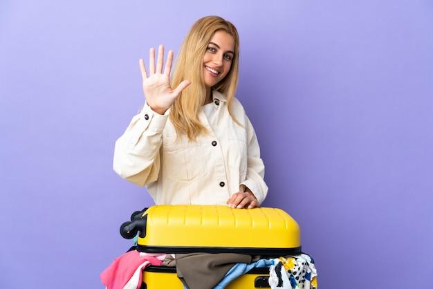 Młoda urugwajska blondynki kobieta z walizką pełną ubrania nad odosobnioną purpurową ścianą liczy pięć z palcami