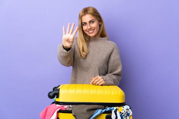 Młoda urugwajska blondynki kobieta z walizką pełną ubrania nad odosobnioną purpury ścianą szczęśliwą i liczącą cztery z palcami