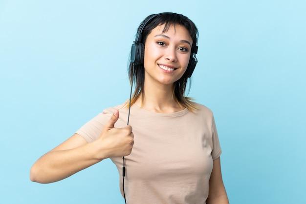 Młoda urugwajska dziewczyna na odosobnionej błękitnej słuchającej muzyce z kciukiem up i