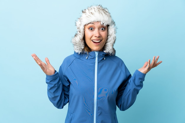 Młoda urugwajska dziewczyna z zima kapeluszem odizolowywającym na błękicie z niespodzianka wyrazem twarzy