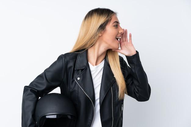 Młoda urugwajska kobieta krzyczy z motocyklowym hełmem nad odosobnioną biel ścianą krzyczy z usta szeroko otwarty