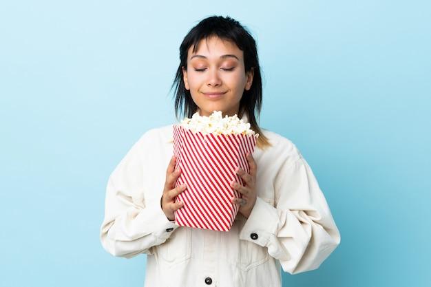 Młoda urugwajska kobieta nad błękitną ścianą trzyma duże wiadro popcorns