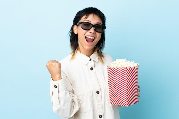 Młoda urugwajska kobieta nad niebieską ścianą z okularami 3d i trzymająca duże wiadro popcornów