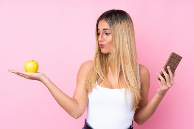Młoda urugwajska kobieta nad odizolowaną różową ścianą ma wątpliwości, biorąc jednocześnie czekoladową tabletkę w jednej ręce i jabłko w drugiej
