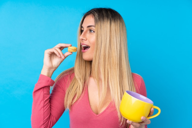 Młoda urugwajska kobieta nad odosobnioną błękit ścianą trzyma kolorowe francuskich macarons i filiżankę mleka