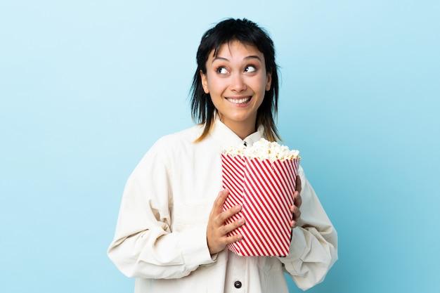 Młoda urugwajska kobieta nad odosobnionym błękitem trzyma dużego wiadro popcorns