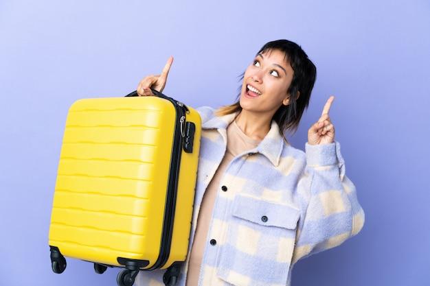 Młoda urugwajska kobieta nad odosobnionymi purpurami w wakacje z podróży walizką i wskazywać up