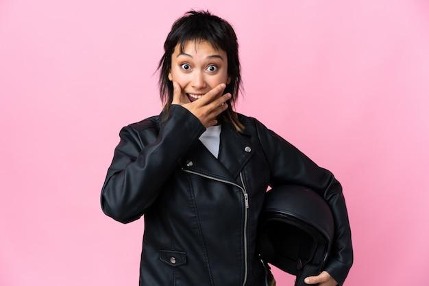 Młoda urugwajska kobieta trzyma motocyklowego hełm nad odosobnionym menchiami z niespodzianka wyrazem twarzy