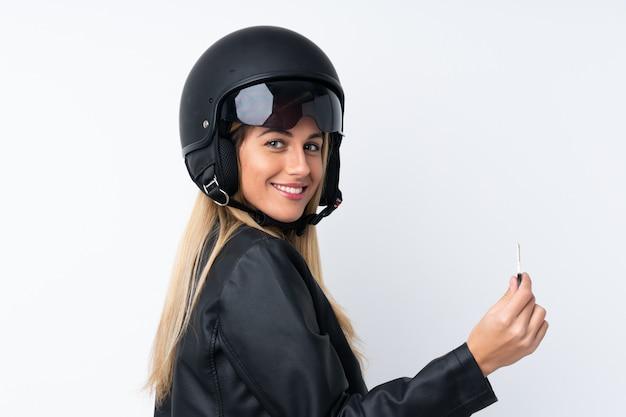 Młoda urugwajska kobieta z motocyklu hełmem nad odosobnioną biel ścianą