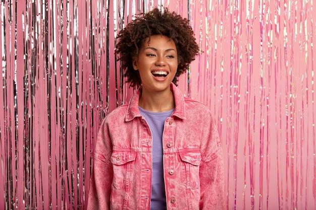 Młoda uśmiechnięta afroamerykanka ma minimalny makijaż, nosi różową kurtkę